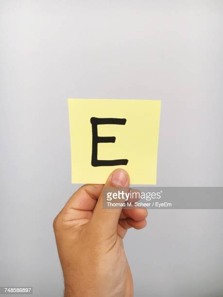 cropped hand of person holding letter e on adhesive note against gray background - letra e - fotografias e filmes do acervo