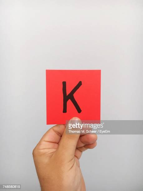 Cropped Hand Of Person Holding Letter K On Adhesive Note Against Gray Background