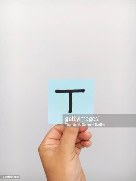 Cropped Hand Of Person Holding Letter T On Adhesive Note Against Gray Background