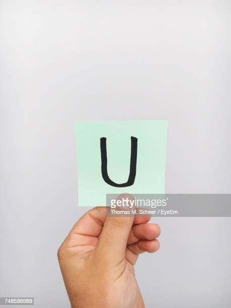 cropped hand of person holding letter u on adhesive note against gray background - letter u stock photos and pictures