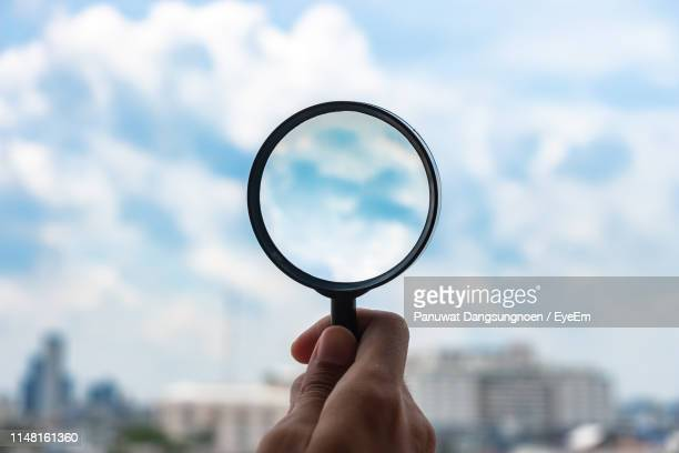 cropped hand of person holding magnifying glass against sky - searching stock pictures, royalty-free photos & images