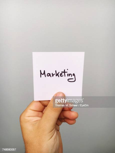 Cropped Hand Of Person Holding Marketing Text On Adhesive Note Against Gray Background