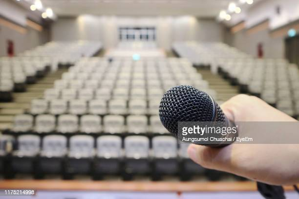 cropped hand of person holding microphone - aungsumol stock pictures, royalty-free photos & images