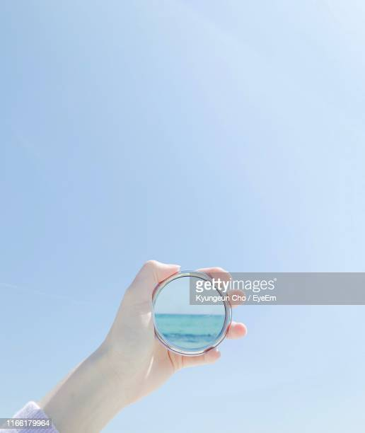 cropped hand of person holding mirror against clear blue sky - jeju - fotografias e filmes do acervo