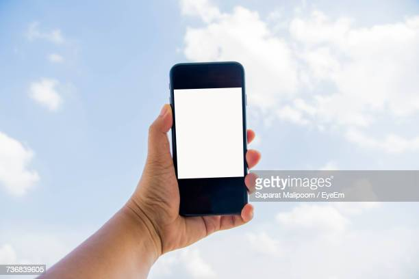 Cropped Hand Of Person Holding Mobile Phone Against Sky