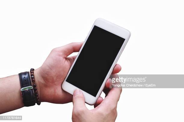 cropped hand of person holding mobile phone against white background - bracelet stock pictures, royalty-free photos & images