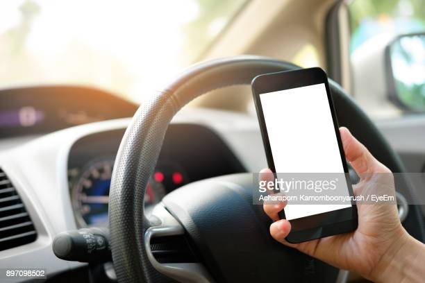Cropped Hand Of Person Holding Mobile Phone In Car