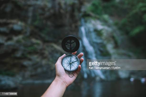 cropped hand of person holding navigational compass against waterfall - compass stock pictures, royalty-free photos & images