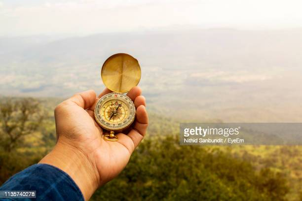 cropped hand of person holding navigational compass - compass stock pictures, royalty-free photos & images