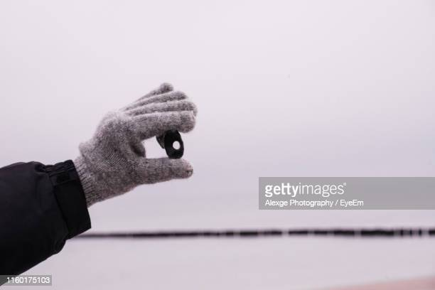 cropped hand of person holding object against sky - mitten stock pictures, royalty-free photos & images