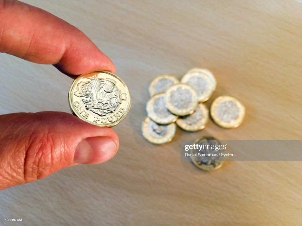 cropped hand of person holding one pound coin over table stock photo
