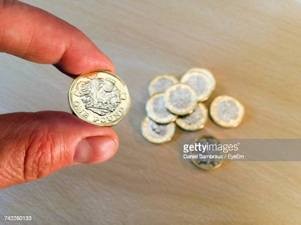 Cropped Hand Of Person Holding One Pound Coin Over Table