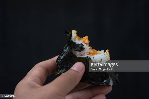 Cropped Hand Of Person Holding Onigiri Against Black Background