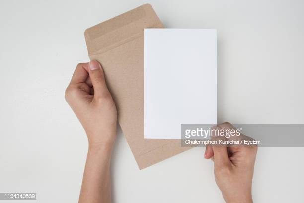 cropped hand of person holding paper over white background - envelope stock pictures, royalty-free photos & images