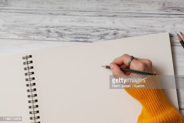 cropped hand of person holding pencil over book on table - florin seitan stock pictures, royalty-free photos & images