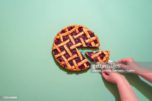 cropped hand of person holding pie slice on blue background - パイ ストックフォトと画像