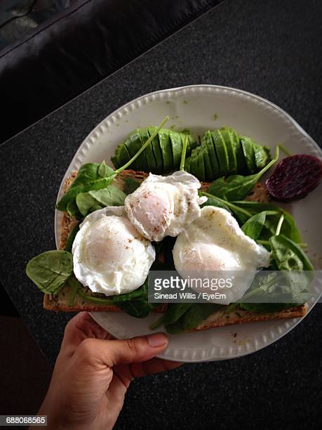 Cropped Hand Of Person Holding Plate Of Poached Eggs And Bread On Table