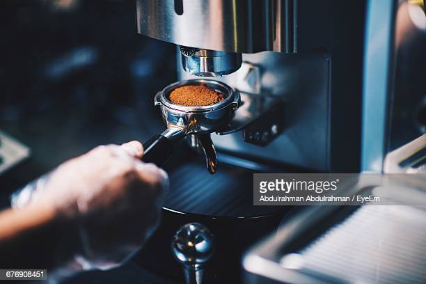 cropped hand of person holding portafilter with ground coffee in cafe - preparation stock pictures, royalty-free photos & images
