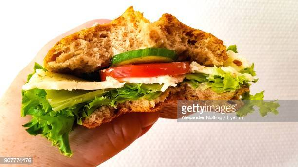 Cropped Hand Of Person Holding Sandwich Against Wall