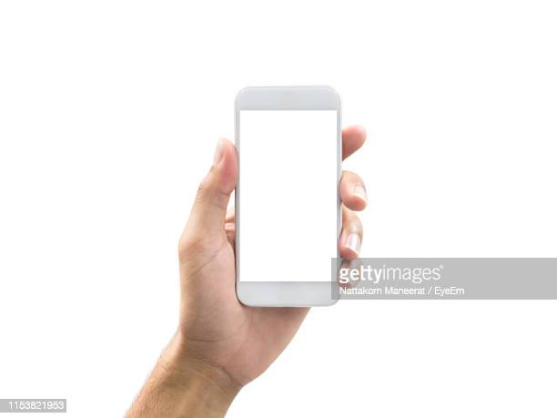 cropped hand of person holding smart phone against white background - menselijke hand stockfoto's en -beelden