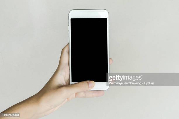 Cropped Hand Of Person Holding Smart Phone Against White Background