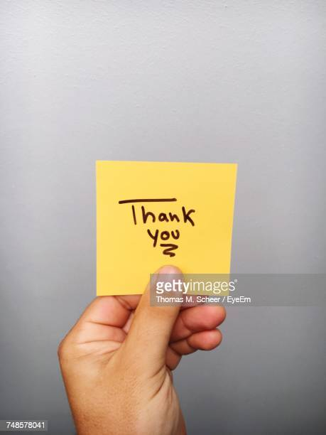 Cropped Hand Of Person Holding Thank You Text On Adhesive Note Against Gray Background
