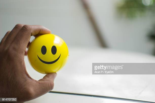 cropped hand of person holding yellow smiley ball - smiley face stock pictures, royalty-free photos & images
