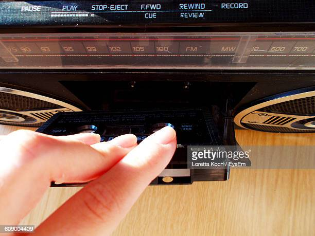 Cropped Hand Of Person Inserting Audio Cassette In Tape Recorder