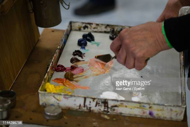 cropped hand of person making acrylic painting on table - acrylic painting stock photos and pictures