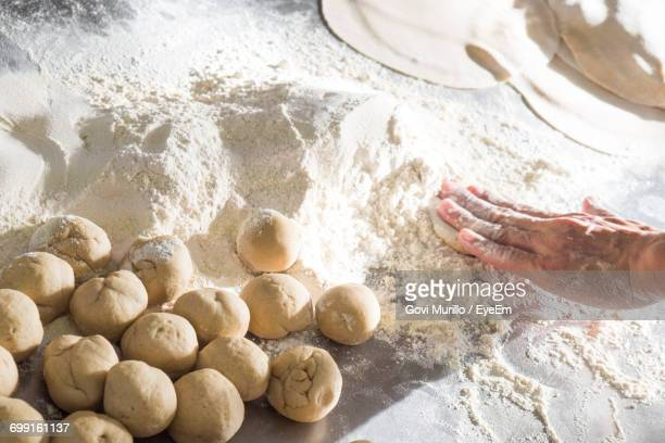 Cropped Hand Of Person Making Chapatti On Counter In Kitchen At Home