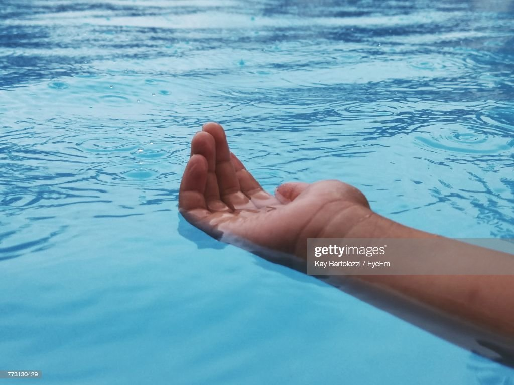 Cropped Hand Of Person On Swimming Pool : Photo