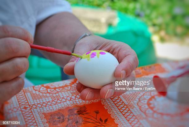 Cropped Hand Of Person Painting Egg On Table