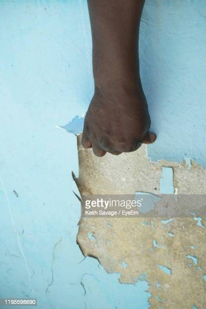 cropped hand of person peeling wall - keith savage stock-fotos und bilder