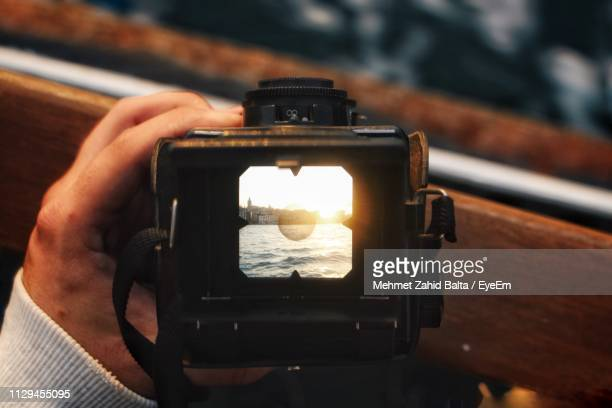 cropped hand of person photographing with camera during sunset - digital viewfinder stockfoto's en -beelden