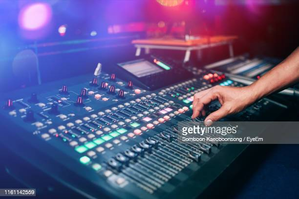 cropped hand of person playing sound mixer at music concert - equalizer stockfoto's en -beelden