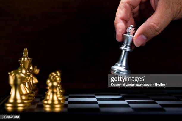 Cropped Hand Of Person Playing With Chess Against Black Background