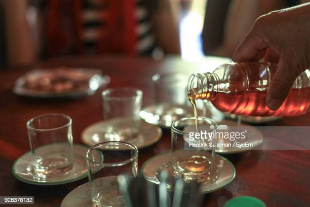 Cropped Hand Of Person Pouring Honey Into Glasses On Table