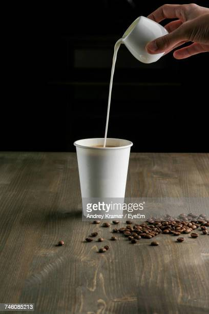 Cropped Hand Of Person Pouring Milk In Disposable Cup By Coffee Beans On Table Against Black Background