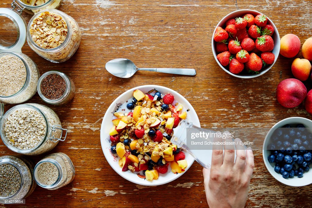 Cropped Hand Of Person Pouring Milk In Fruits On Table : Foto de stock
