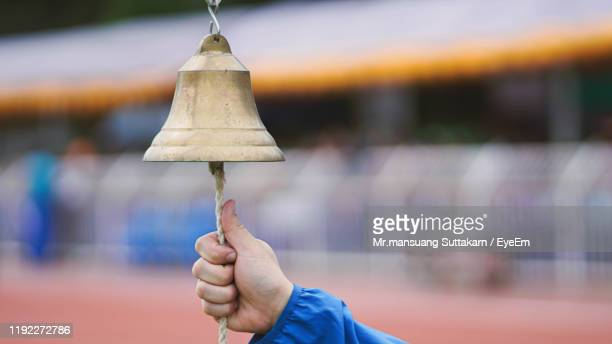 cropped hand of person ringing bell - bell stock pictures, royalty-free photos & images