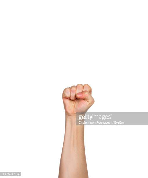 cropped hand of person showing fist against white background - poing photos et images de collection