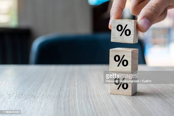 cropped hand of person stacking toy blocks on table - percentage sign stock pictures, royalty-free photos & images