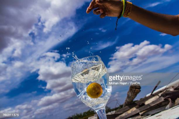 Cropped Hand Of Person Throwing Lemon In Drink Against Cloudy Sky During Sunny Day