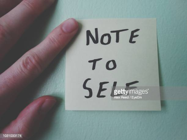 cropped hand of person touching adhesive note on wall - reminder stock pictures, royalty-free photos & images