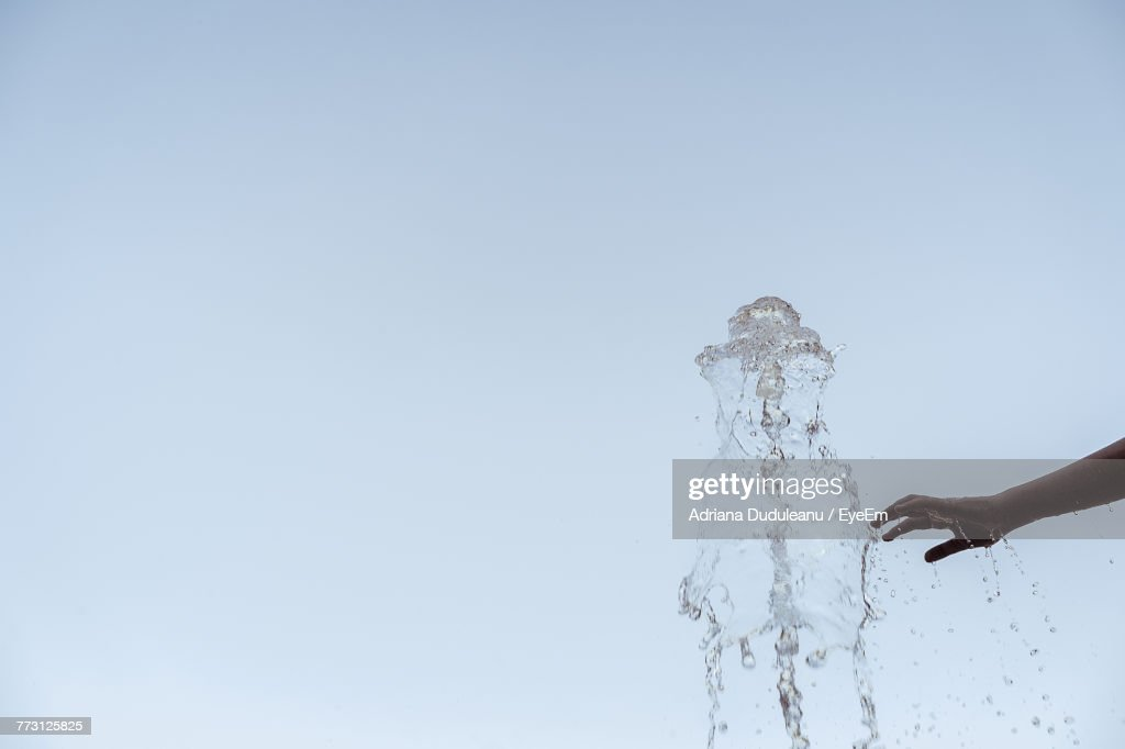 Cropped Hand Of Person Touching Splashing Water Against Clear Sky : Stock Photo