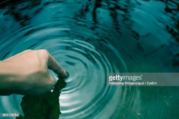 Cropped Hand Of Person Touching Water