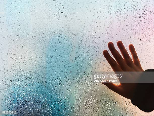 Cropped Hand Of Person Touching Wet Window