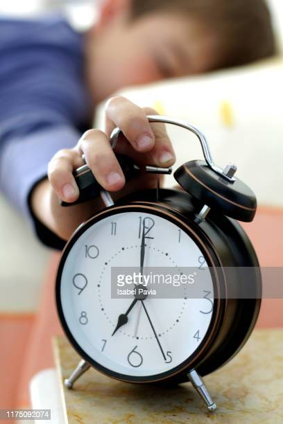 cropped hand of person turning off alarm clock - 6 7 años fotografías e imágenes de stock