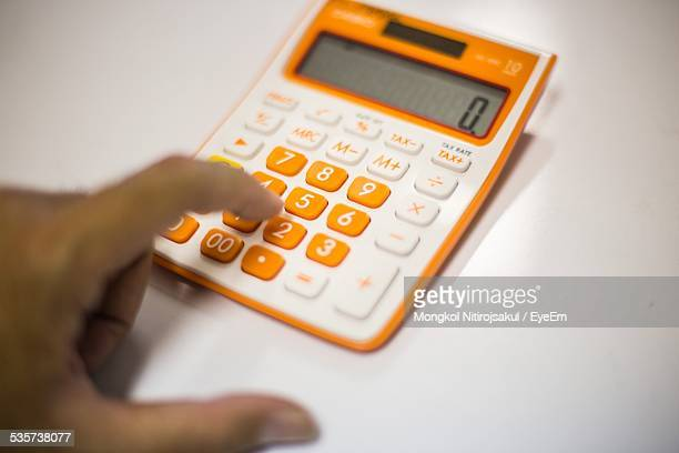 Cropped Hand Of Person Using Calculator On White Table