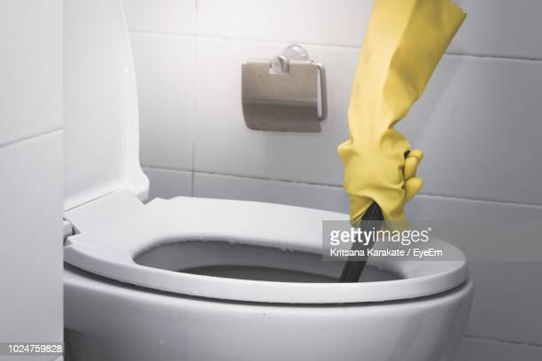 cropped hand of person wearing yellow protective glove while washing toilet bowl - cuvette photos et images de collection